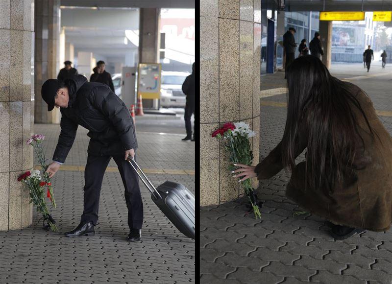 В аэропорт Алматы приходят люди с цветами в знак скорби по погибшим
