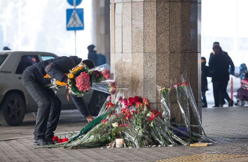 Мужчина забирал цветы, сложенные в память о погибших в авиакатастрофе в Алматы