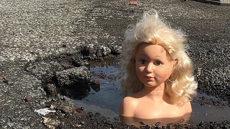 Мужчина заделал дыру на дороге, используя кукольные головы